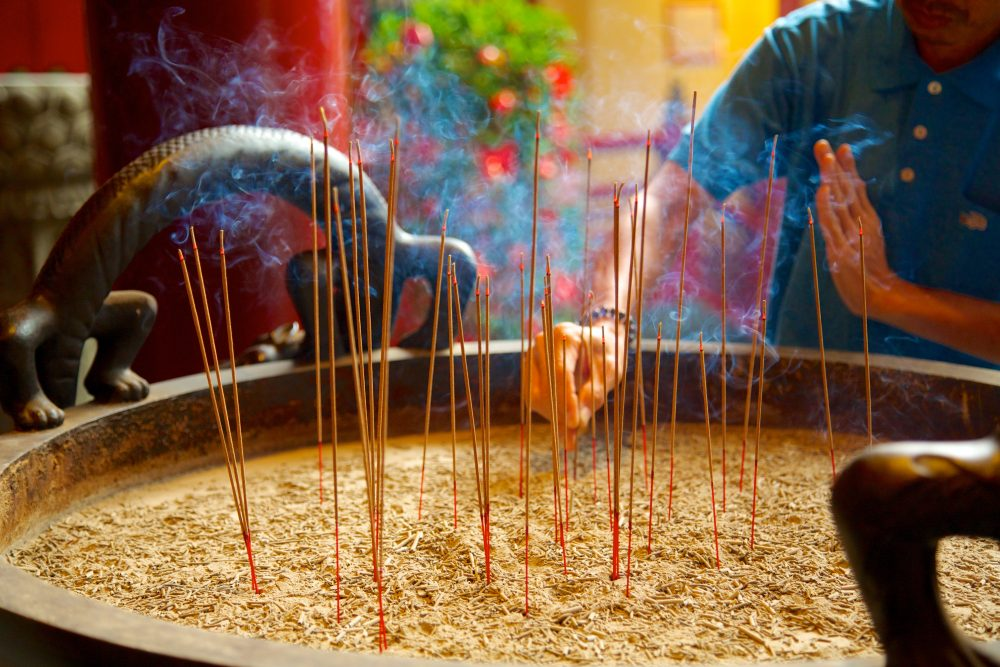 View of a man lighting incense sticks in Chinatown