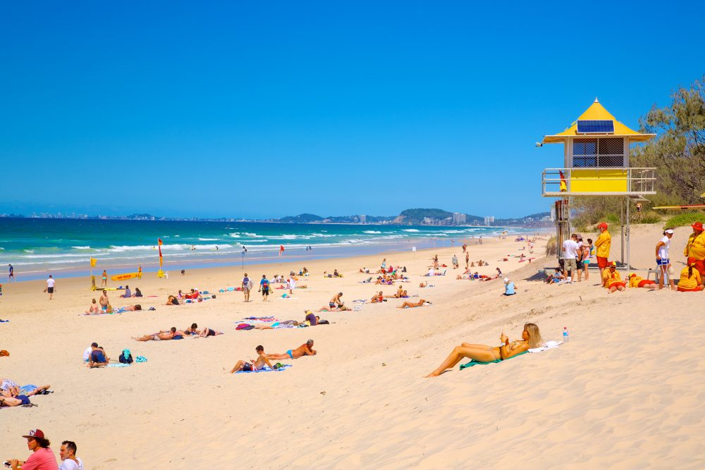 Beachgoers relax in the sunshine on a wide strip of Kurrawa Beach with a yellow lifeguard station in the background