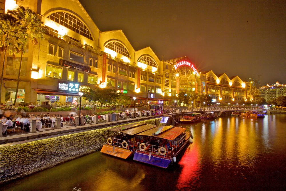 Nighttime view of restaurants lining the water at Clarke Quay Mall