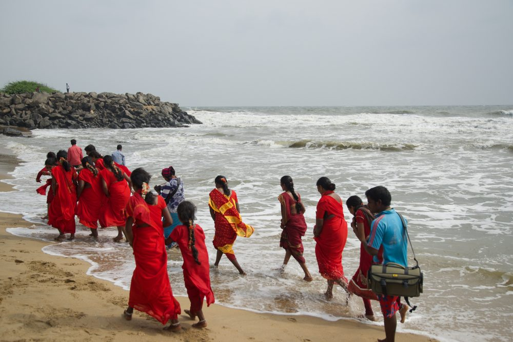 Women in red walk as a group in the surf along Mamallapuram Beach in Chennai