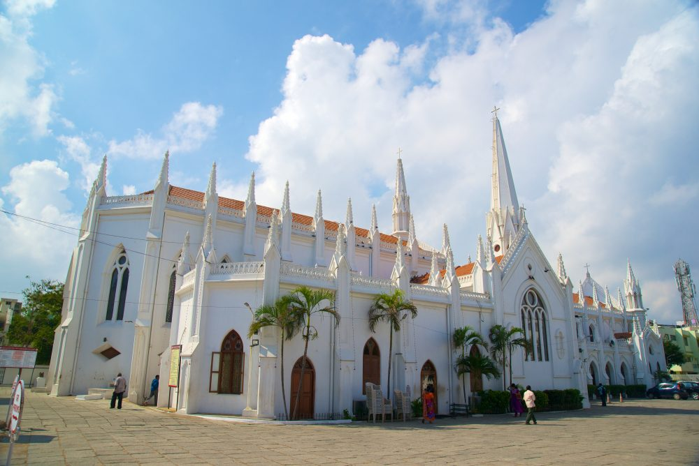 The San Thome cathedral, a white cathedral built in the Neo-Gothic style, with many spires and Gothic windows stands amid a stone plaza in Chennai